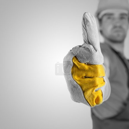 Photo for Construction worker or builder in a protective hardhat and gloves giving a thumbs up gesture of approval and success with selective focus to his gloved hand , greyscale image with yellow and copyspace - Royalty Free Image