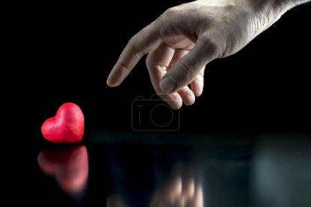Photo pour Homme pointant vers un cœur rouge couché sur une surface réfléchissante symbolisant l'amour et la romance pour un amour ou un amant ou d'un mode de vie sain exempt de complications médicales - image libre de droit