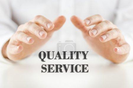 Photo pour Image conceptuelle décrivant le service fiable qualité et satisfaction à la clientèle et soutien garanti avec une mans main embouti protégée sur le texte - un service de qualité. - image libre de droit
