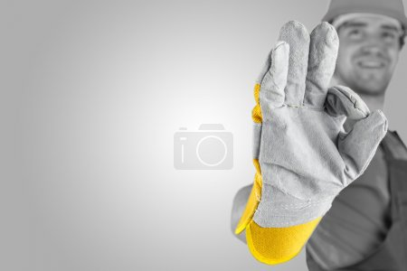 Photo for Workman making a perfect gesture with his gloved hand with focus to his hand over a grey background with a highlight and copyspace. - Royalty Free Image