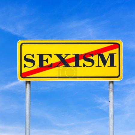 Photo pour Interdiction du sexisme panneau avec le mot Sexisme traversé en rouge sur un panneau de circulation jaune sur un ciel bleu conceptuel de l'égalité des sexes . - image libre de droit