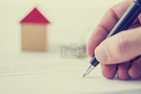 Photo pour Image rétro d'un homme signant un acte de vente, hypothèque ou un contrat d'assurance sur une maison avec une vue de plan rapproché de sa main avec un petit modèle en bois d'une maison. - image libre de droit