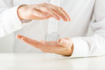 Photo pour Homme tasses ses mains dans un geste de protection au-dessus et en dessous d'un espace vide pour votre placement de produit ou objet conceptuel, vue rapprochée des mains contre une chemise blanche . - image libre de droit