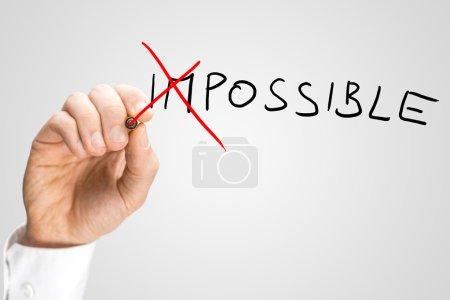 Photo pour Homme traversant la GI dans le mot manuscrite impossible sur un écran virtuel avec un stylo feutre rouge dans un concept d'opposés pour impossible - possible. - image libre de droit