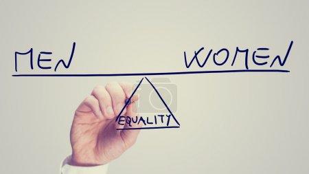 Photo pour Égalité entre les hommes et les femmes, image conceptuelle du statut des droits de la femme avec un homme dessinant une balançoire sur une interface virtuelle équilibrant les deux concepts à des extrémités opposées en équilibre . - image libre de droit