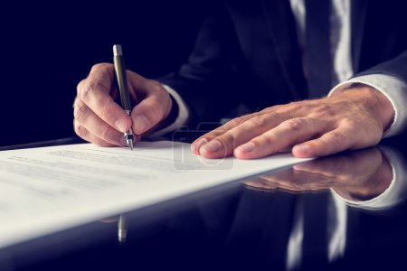 Photo for Retro image of lawyer signing important legal document on black desk. Over black background. - Royalty Free Image