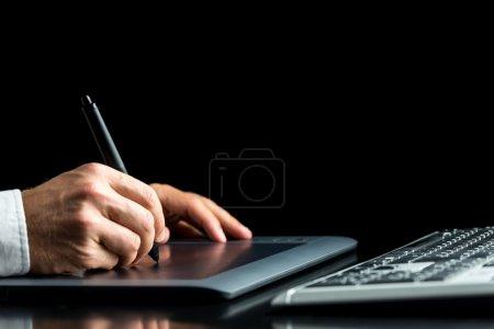 Photo pour Gros plan de travail de concepteur graphique mâle sur sa tablette numérique sur fond noir. - image libre de droit