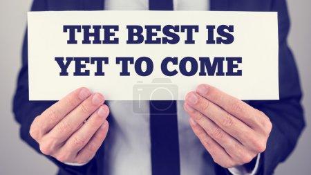 Photo pour Mains masculines tenant une carte blanche avec message de motivation Le meilleur reste à venir, avec effet filtre rétro . - image libre de droit