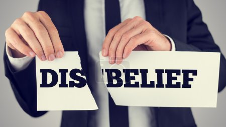 Man holding torn paper with the words Dis-Belief