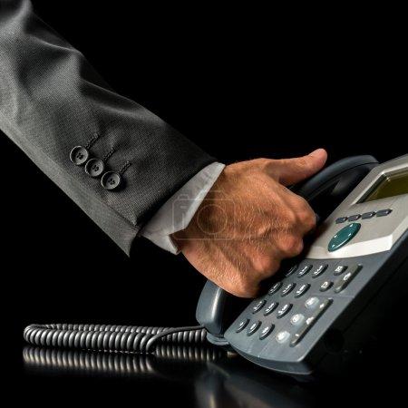 Photo pour Gros plan de la main d'un homme d'affaires prenant le récepteur d'un téléphone fixe noir, placé sur le bureau, avec espace de copie sur noir - image libre de droit