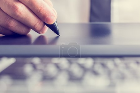 Photo for Retro image of male hand of a designer drawing with the stylus on a grey graphics tablet, close-up. - Royalty Free Image