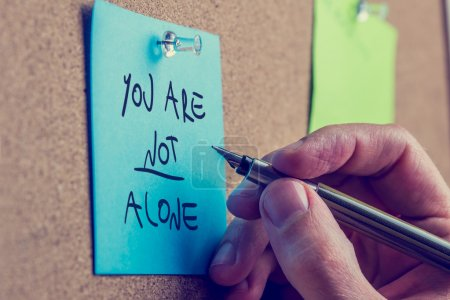 Photo for You Are Not Alone - man writing an inspirational message on a blue sticky note pinned to a cork board with a fountain pen. - Royalty Free Image
