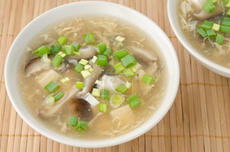 Two bowls of chinese spicy soup with egg, shiitake...