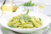 Pasta penne with sauce of arugula and green peas close-up