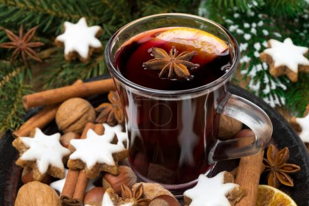 cup of mulled wine, cookies in the shape of stars and spices
