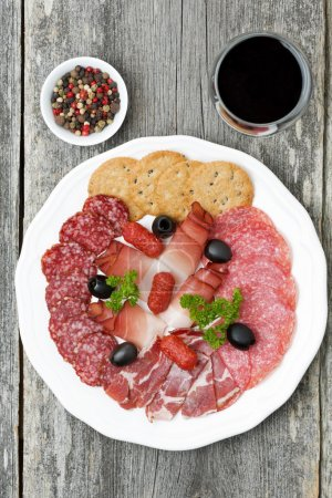 assorted deli meats and a glass of wine, top view