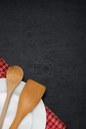 Photo for Empty plate and spoon in the corner on a blackboard, vertical - Royalty Free Image