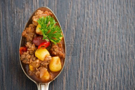 Spicy Mexican dish chili con carne in a spoon