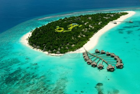 Maldivian island with water villas from airplan view