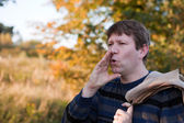 Young man shouting in autumn forest on sunny day