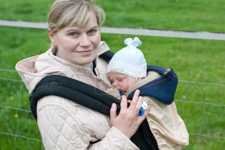 Young mother carrying little baby in rucksack in park