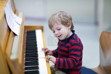 Photo pour Deux ans heureux tout-petit garçon jouer du piano - image libre de droit