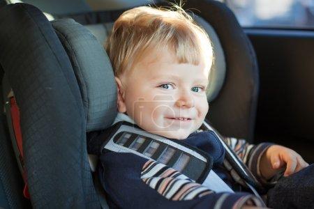 Photo pour Adorable petit garçon aux yeux bleus en siège auto sécurité - image libre de droit