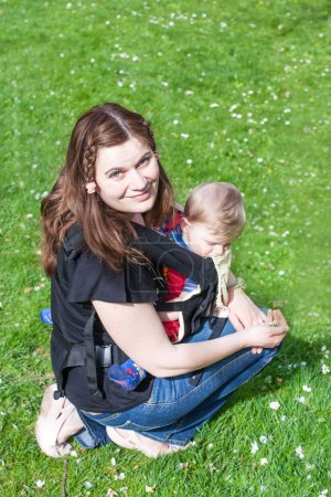Young woman carrying baby in rucksack in park