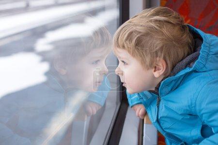 Cute little boy looking out train window