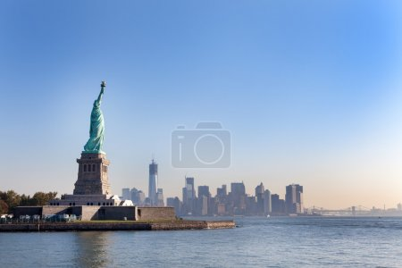 Photo for The Statue of Liberty free of tourists and New York City Downtown on sunny early morning - Royalty Free Image