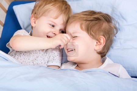 Two little toddler boys having fun in bed
