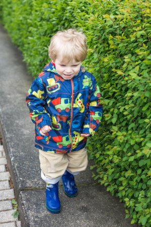 Little toddler boy in rain clothes, outdoors