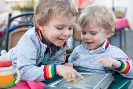 Two brother toddler boys playing with tablet pc