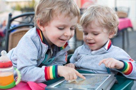 Foto de Dos niños jugando con tablet pc, al aire libre - Imagen libre de derechos