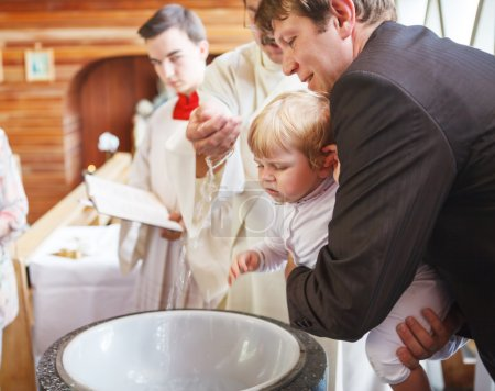 Little baby boy being baptized in catholic church holding by fat