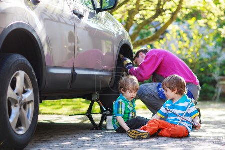 father and two little boys repairing car and changing wheel toge