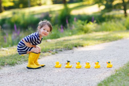 Adorable little girl of 2 playing with yellow rubber ducks in su