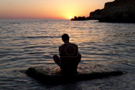 Photo pour L'homme méditant en bord de mer au coucher du soleil - image libre de droit
