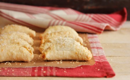 Photo for Homemade apple and cinnamon hand pies with cheddar cheese and sugar on top on a kitchen towel on a wooden board - Royalty Free Image