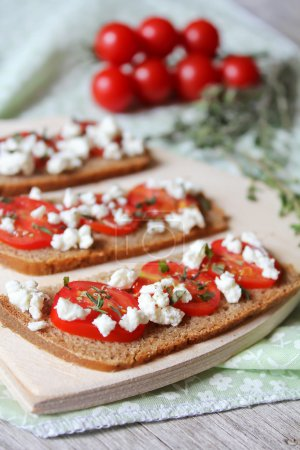 Rye bread bruschetta with sliced cherry tomatoes, crumbled cottage cheese and dried thyme on a wooden board for breakfast or summer picnic snack