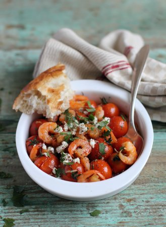 Traditional mediterranean dish with roasted roma tomatoes, garlic prawns, crumbled feta cheese and chopped fresh parsley in a bowl ready for lunch and healthy dinner