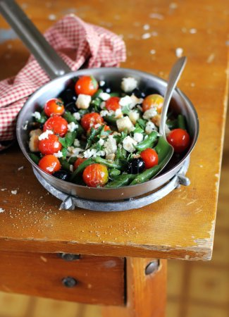 Salad with blanched green french beans, roasted cherry tomatoes, crumbled feta cheese, black olives, crispy wheat croutons in a pan, selective focus, mediterranean style