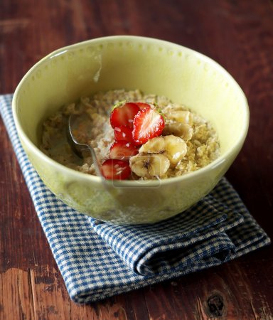 Bowl of oatmeal porridge served with fresh chopped strawberry, banana slices and freshly shredded coconut for morning breakfast or healthy snack, selective focus