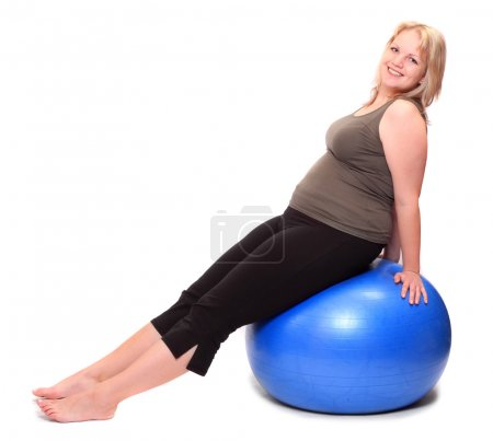 Overweight young woman sitting on blue fitness ball