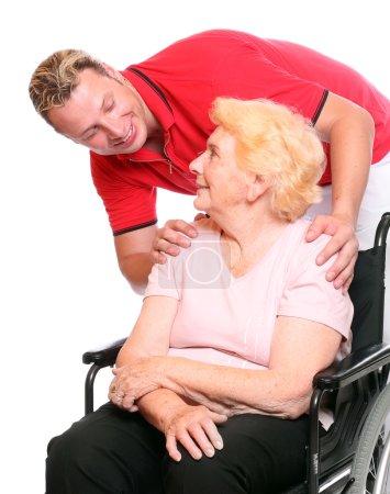 Elderly paraplegic woman sitting in a wheelchair and her male nurse
