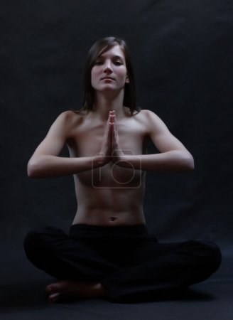 Low key portrait of a young topless beautiful woman in yoga position