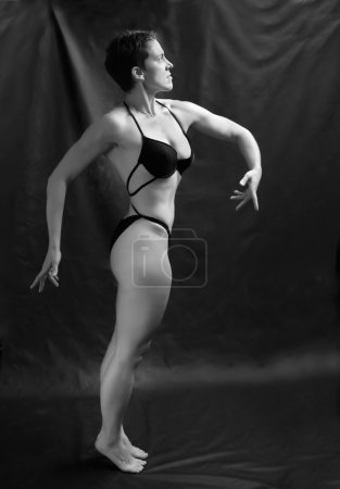 Body builder woman posing on black background.