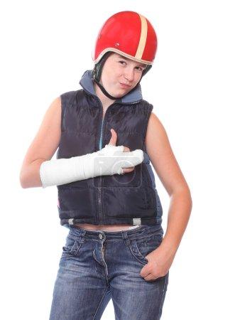 Teenager in protective helmet with broken arm. Insurance metaphor.