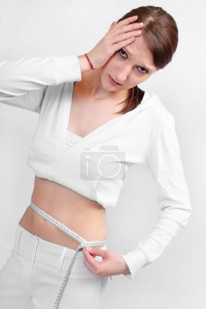 Close up of young woman measure her waist belly by metre-stick.