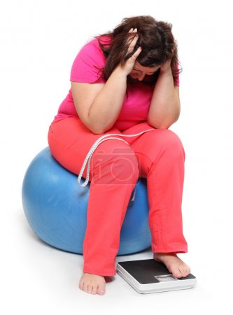 Photo for Overweight woman with weighing machine, sad, sitting on ball - Royalty Free Image